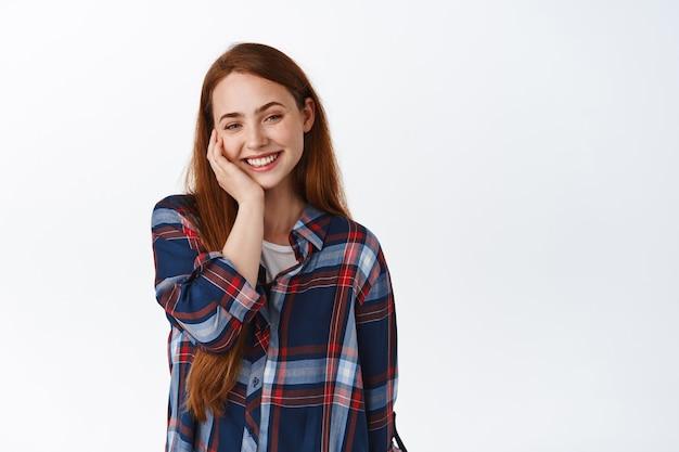 Linda garota romântica com cabelos compridos ruivos, corando e sorrindo encantada de pé no branco