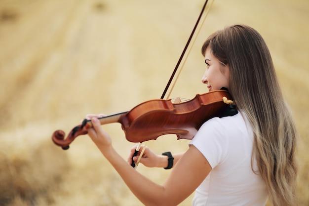 Linda garota romântica com o cabelo solto tocando violino no campo após a colheita