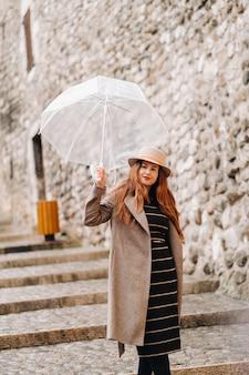 Linda garota romântica com um casaco e um chapéu com um guarda-chuva transparente em annecy