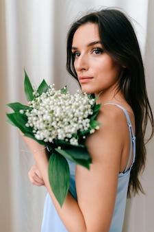 Linda garota romântica em pijamas posando com flores