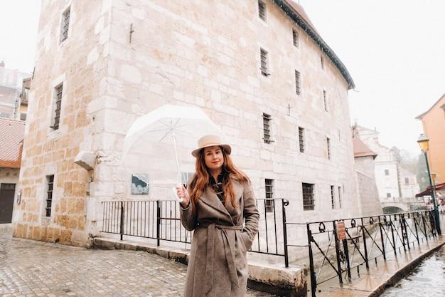 Linda garota romântica em um casaco e um chapéu com um guarda-chuva transparente em annecy. frança. a garota de chapéu na frança.