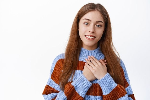 Linda garota romântica segurando o coração de mãos dadas, sorrindo e suspirando de coração, expressar gratidão, dizer obrigado, em pé sobre uma parede branca