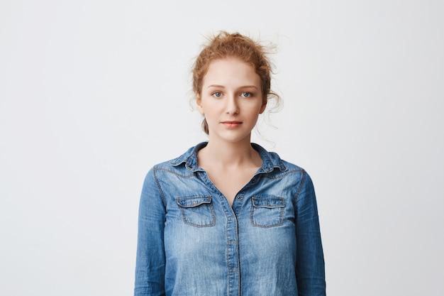 Linda garota ruiva adolescente com cabelo penteado e lindos olhos azuis em pé na camisa jeans sobre espaço cinza, expressando humor calmo e relaxado