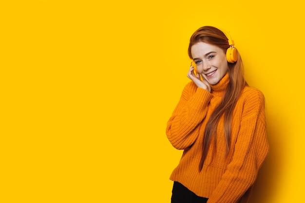 Linda garota ruiva caucasiana com sardas usando fones de ouvido posando em uma parede amarela com espaço livre