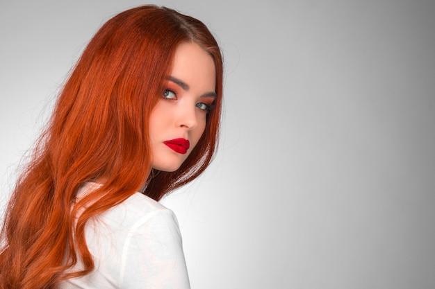 Linda garota ruiva com cabelo ondulado retrato de estúdio de beleza