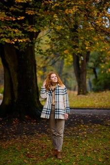 Linda garota ruiva com cabelos cacheados e olhos azuis. uma garota caminha pelo parque outono.