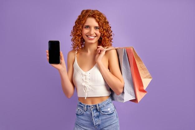 Linda garota ruiva com cachos e sacolas de compras mostra a tela em branco do smartphone isolada em roxo. compras online. venda