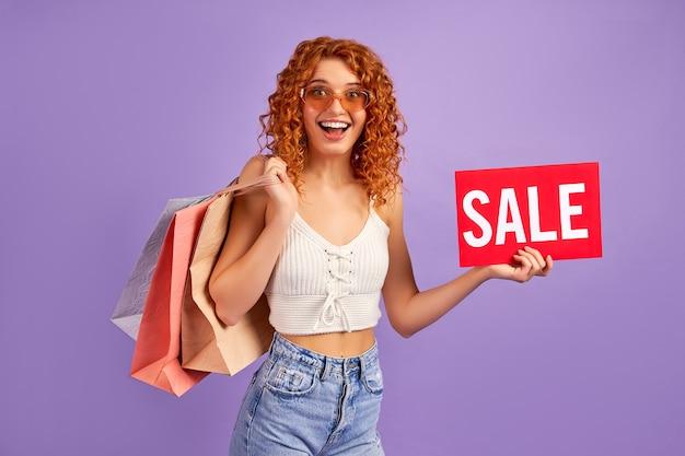 Linda garota ruiva com cachos e sacolas de compras, segurando um cartaz com a inscrição venda isolada no roxo. compras online. venda