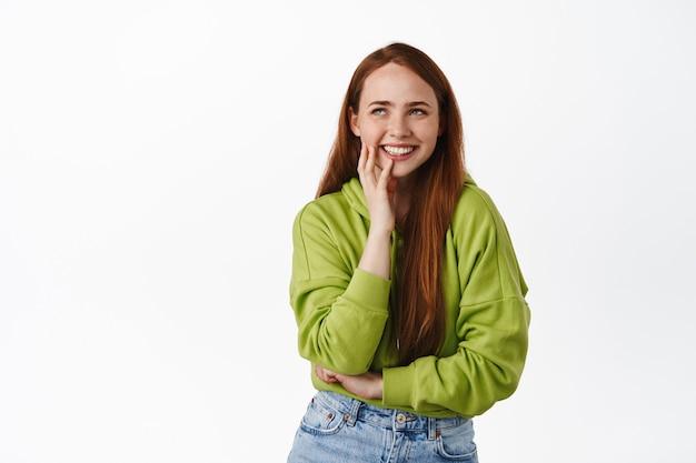 Linda garota ruiva com pele pálida e sardas e rindo feliz, em pé com capuz e jeans branco.