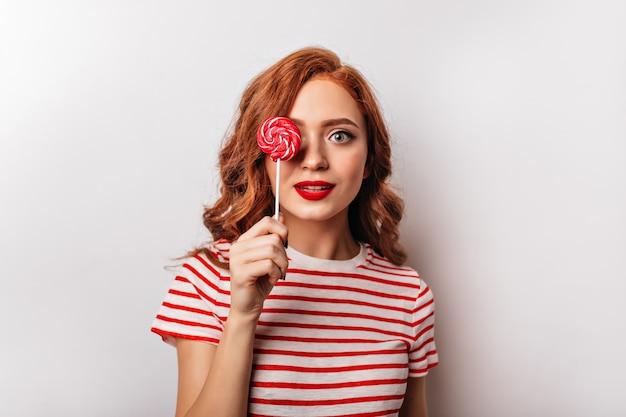 Linda garota ruiva com pirulito posando na parede branca. jovem atraente segurando bala vermelha.