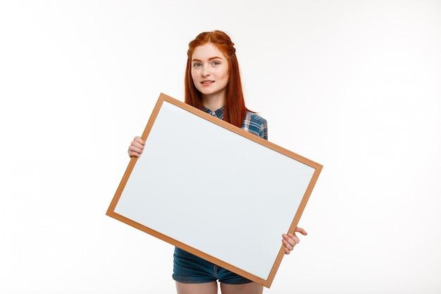 Linda garota ruiva com quadro branco muro branco.