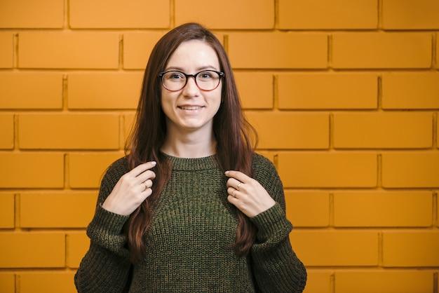 Linda garota ruiva de óculos e um suéter verde está sorrindo contra uma parede de tijolos amarelos