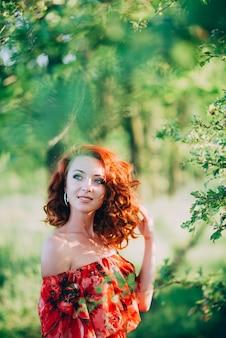 Linda garota ruiva de vestido vermelho entre a folhagem verde da árvore sorrindo.