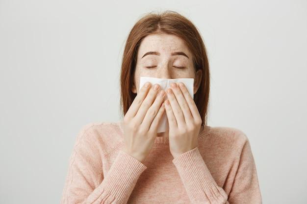 Linda garota ruiva doente com alergia espirrando em guardanapo