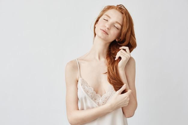 Linda garota ruiva em roupa de noite sorrindo com os olhos fechados.