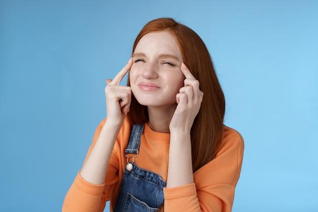 Linda garota ruiva europeia engraçada esqueceu os óculos tentando ler suspiro esticar as pálpebras apertando os olhos franzindo a testa focado no canto superior esquerdo perplexo ver o que está acontecendo, em pé de fundo azul.