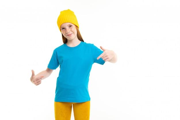 Linda garota ruiva europeia mostra uma camiseta mock-up na parede branca