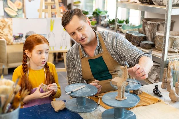 Linda garota ruiva fazendo perguntas ao professor de arte sobre argila