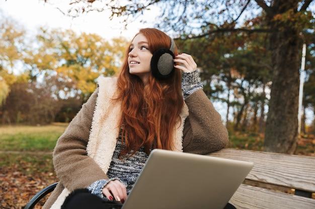 Linda garota ruiva ouvindo música com headpones enquanto está sentada em um banco, usando um laptop