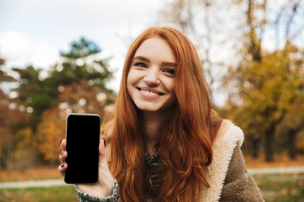 Linda garota ruiva ouvindo música enquanto está sentada em um banco, usando o telefone celular, mostrando a tela do celular