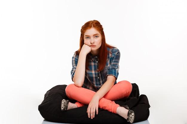 Linda garota ruiva sentada de pernas cruzadas sobre parede branca.