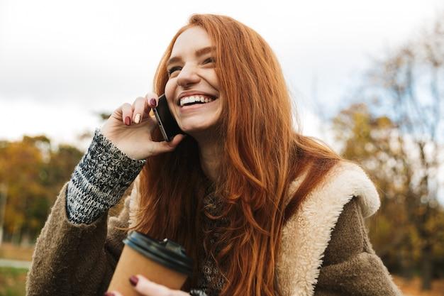 Linda garota ruiva sentada em um banco, usando telefone celular