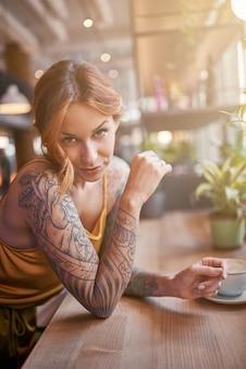Linda garota ruiva tatuada no café