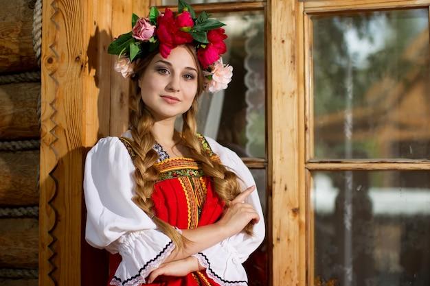 Linda garota russa com uma foice e uma coroa na cabeça em vestido nacional.