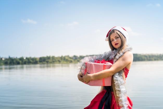 Linda garota santa segurando uma caixa de presente na praia