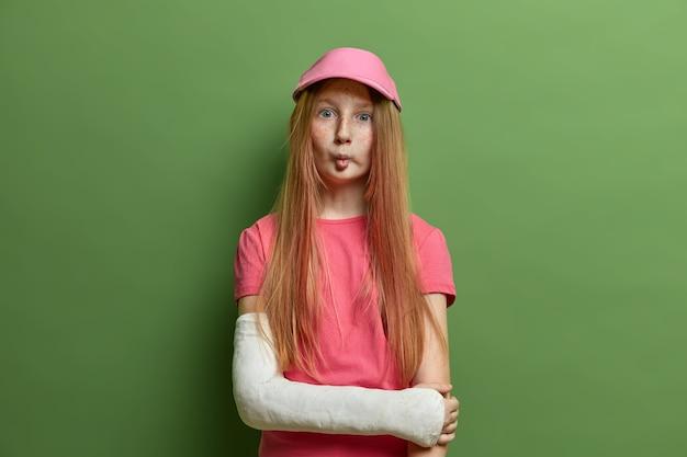 Linda garota sardenta faz uma careta engraçada, lábios de peixe, tem cabelo ruivo longo e liso, usa boné rosado e camiseta, braço quebrado engessado, fica contra a parede verde. crianças, expressões faciais, acidente