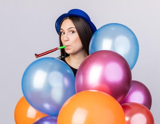 Linda garota satisfeita com um chapéu de festa segurando balões e soprando um apito de festa