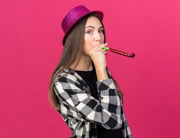 Linda garota satisfeita com um chapéu de festa soprando um apito isolado na parede rosa