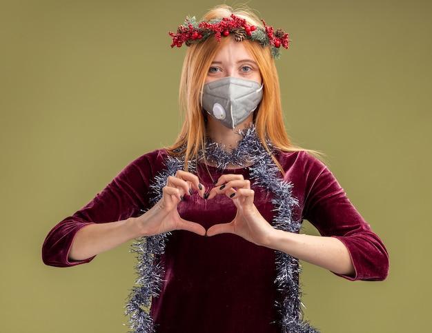 Linda garota satisfeita com um vestido vermelho com coroa de flores e máscara médica com guirlanda no pescoço, mostrando gesto de coração isolado em fundo verde oliva