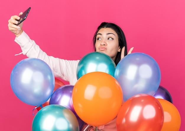 Linda garota satisfeita em pé atrás de balões, tirando uma selfie mostrando um gesto de paz isolado na parede rosa