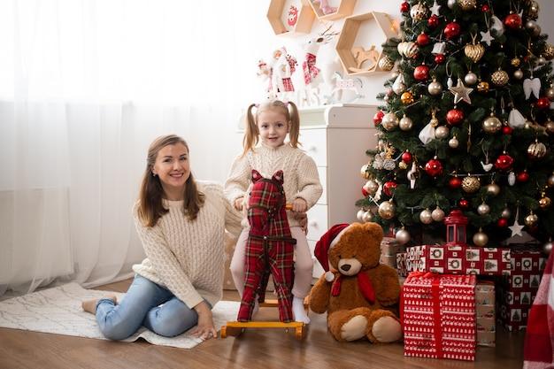 Linda garota se divertindo com a mãe em casa perto de árvore de natal