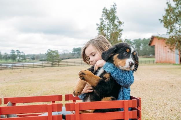 Linda garota se divertindo com seu cachorrinho criança feliz e animal de estimação na carroça vermelha