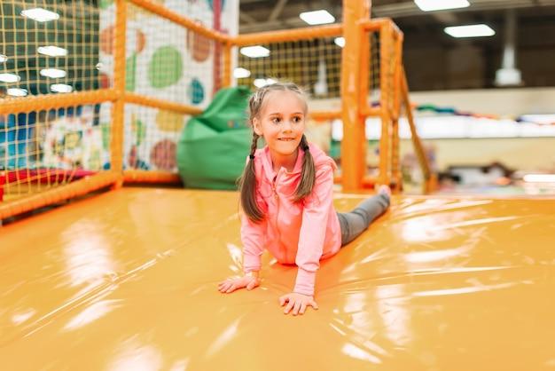 Linda garota se divertindo na atração inflável no centro de entretenimento infantil. infância feliz