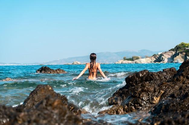 Linda garota se divertindo no mar, horário de verão