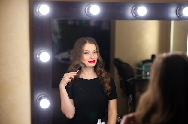 Linda garota se maquia e se olha no espelho