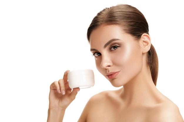 Linda garota se preparando para começar o dia. ela está aplicando creme hidratante no rosto.