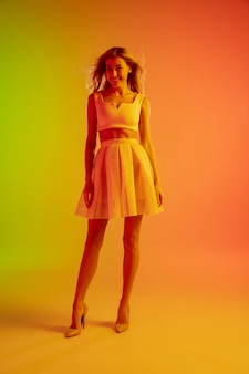 Linda garota sedutora com roupa elegante e romântica em fundo gradiente verde-laranja brilhante com luz de néon.
