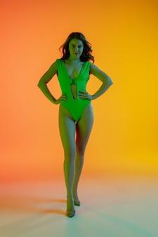 Linda garota sedutora em um maiô verde elegante em fundo gradiente amarelo-laranja brilhante.