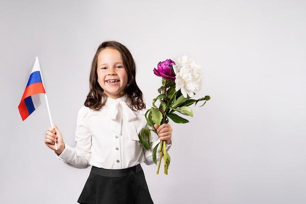 Linda garota segura uma bandeira em uma mão, flores na outra.