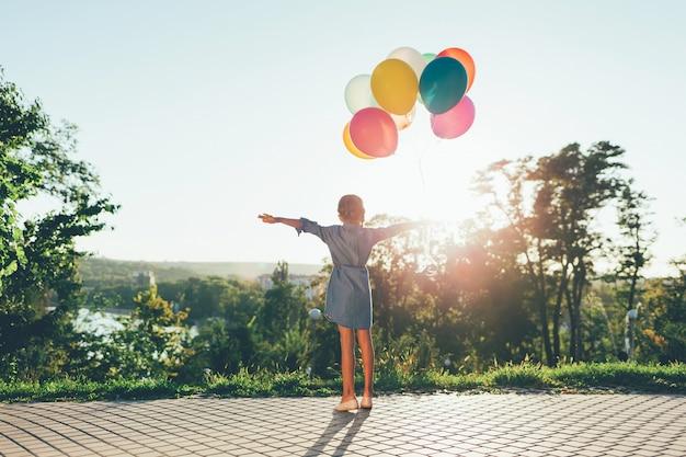 Linda garota segurando balões coloridos no parque da cidade