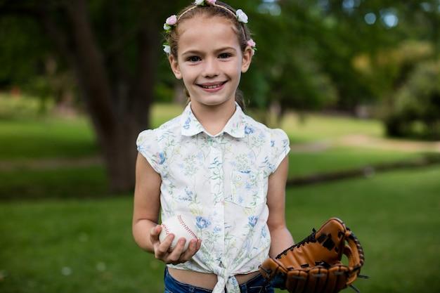 Linda garota segurando beisebol no parque