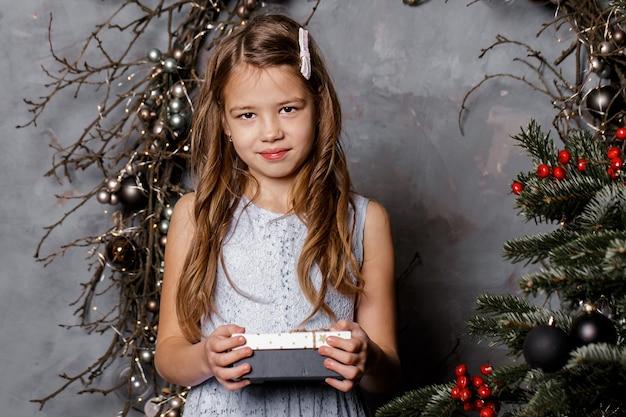 Linda garota segurando caixas de presente de natal e sorrindo na frente da árvore de natal