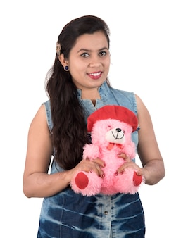 Linda garota segurando e brincando com um ursinho de pelúcia brinquedo em uma parede branca.