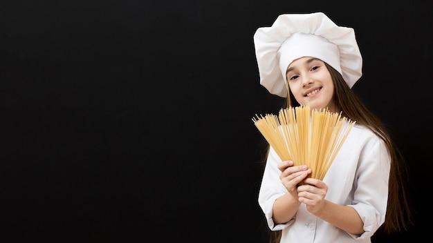 Linda garota segurando espaguete cru