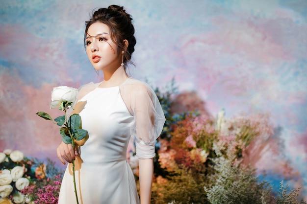 Linda garota segurando flor branca
