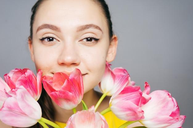 Linda garota segurando lindas flores cor de rosa, apreciando o perfume
